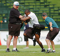 Philadelphia Eagles head coach Andy Reid, left, and Head Althletic Trainer Rick Burkholder, right, put running back Correll Buckhalter through a workout at the team's football camp Sunday, July 23, 2006 in Bethlehem, Pa. Buckhalter has missed three of the last four seasons due to injuries. (AP Photo/Bradley C Bower)