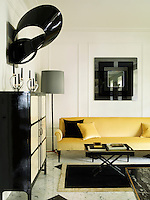 The dining room has an eclectic mix of retro pieces. A Jacques Grange sofa is upholstered in a yellow velvet by Bruno Triplet, the 1960s mirror, which hangs above, is by Pierre Cardin. A striking acrylic sculpture Black Symphony hangs above a 1940's cabinet by Paolo Buffa. The acrylic cocktail table is from the 1970s and the brass and leather floor lamp from the 1950s.