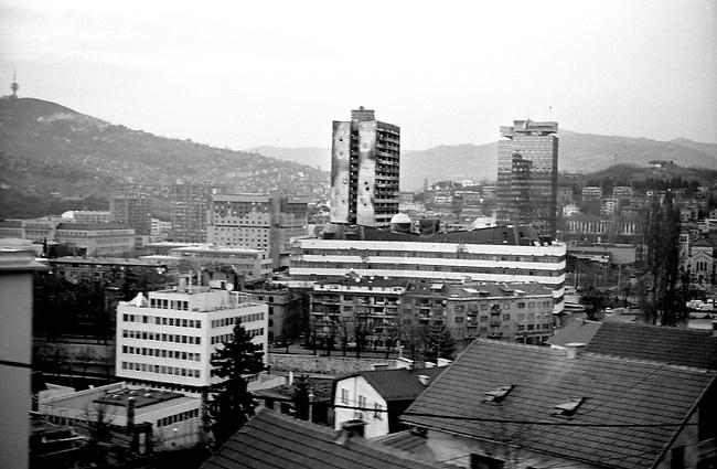 BOSNIA-HERZEGOVINA, Belgrade-Sarajevo Road, 03/2003..Lanscape pictures taken from the bus at Sarajevo. .In the center : the parliament building destroyed diring the war. On the left : the Holiday Inn where the snippers were during the war. On the left low part : the Hight Representant of the international community Headquarter. .BOSNIE-HERZEGONVINE, Route Belgrade-Sarajevo, 03/2003..Photo prise depuis le bus qui relie Belgrade à Sarajevo. Au centre : le batiment abitant le parlement détruit pendant la guerre. En bas à gauche : le quartier général du Haut Représentant de la Communauté Internationale..© Bruno Cogez