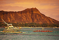 Outrigger canoes and a charter fishing boat cruise past Diamond Head and Waikiki Beach.