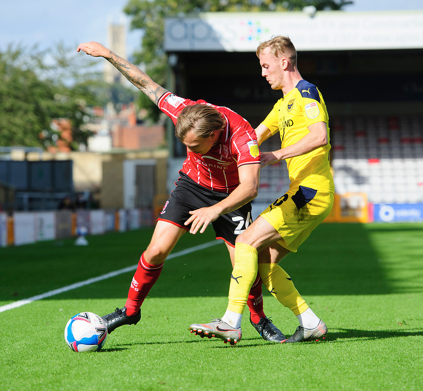 Lincoln City's Harry Anderson vies for possession with Oxford United's Mark Sykes<br /> <br /> Photographer Chris Vaughan/CameraSport<br /> <br /> The EFL Sky Bet League One - Saturday 12th September 2020 - Lincoln City v Oxford United - LNER Stadium - Lincoln<br /> <br /> World Copyright © 2020 CameraSport. All rights reserved. 43 Linden Ave. Countesthorpe. Leicester. England. LE8 5PG - Tel: +44 (0) 116 277 4147 - admin@camerasport.com - www.camerasport.com - Lincoln City v Oxford United