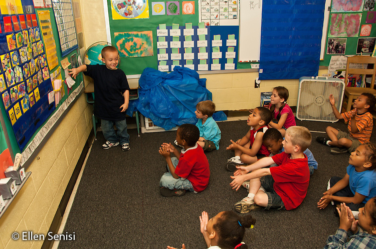 MR / Schenectady, New York. Elmer Avenue School (urban public elementary school). Kindergarten classroom. Student (boy, age 5) leads class in reading basic sight words. This is a daily ritual to help class recognize and memorize basic sight words. MR: Roz1. ID: AH-gKg. ©Ellen B. Senisi