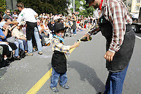 Switzerland. Canton of Neuchâtel. Neuchâtel. Grape Harvest Festival. A young boy, dressed as a cowboy, helps his father who offers free glasses of local wine to the Public. © 2006 Didier Ruef