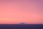 A pink sky and a lonely iceberg on Greenland's West coast.