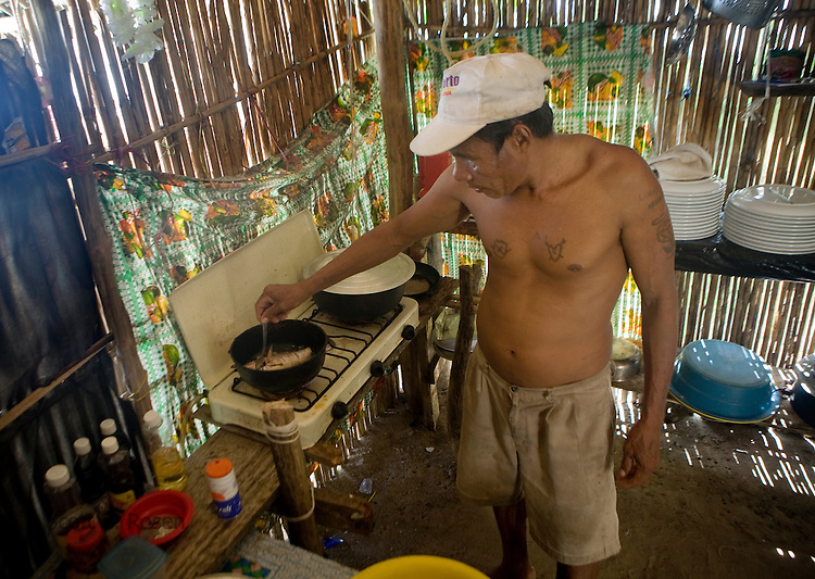A local Kuna man cooks fresh jackfish in oil on Isla Pelikano, San Blas Islands, Kuna Yala, Panama