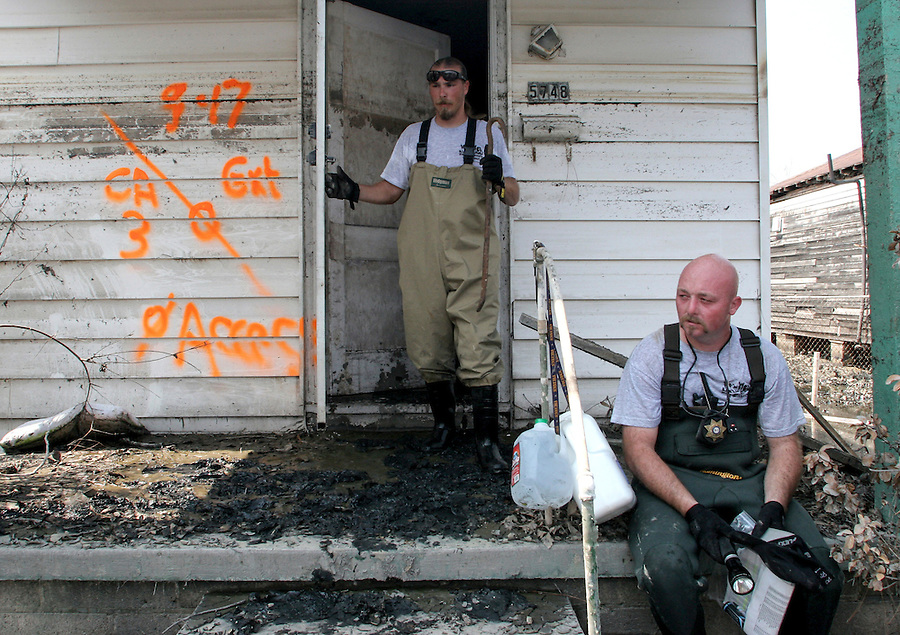 Tim Rickey and Brett Huff, of the Humane Society of Missouri, take a brief break after searching homes for surviving pets in New Orleans three weeks after Hurricane Katrina destroyed the city. The orange markings on the wall were spray painted by body search teams to indicate when the home was searched, by whom, whether they were able to access the home and how many bodies were found. 9/19/05 Julia Cumes