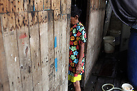 A woman stands in a doorway in central Jakarta. It is estimated over 25% of Indonesians live in slum areas, with more than 5 million people living in slum areas in the greater Jakarta area.