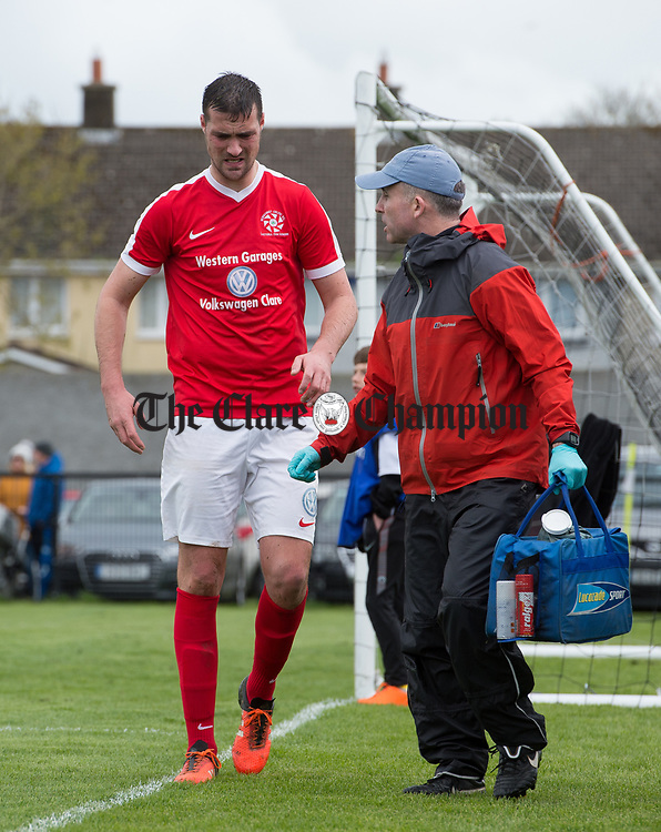Stephen Kelly of Newmarket Celtic goes off injured during their Munster Junior Cup semi-final at Limerick. Photograph by John Kelly.