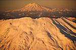 A plume of ash rises above Mount St. Helens; Mount Rainier dominates the horizon,  Washington.
