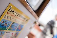Schild zu Verhaltensweisen im Falle eine Notfalls auf einer Barkasse im Hamburger Hafen.<br /> 12.4.2015, Hamburg<br /> Copyright: Christian-Ditsch.de<br /> [Inhaltsveraendernde Manipulation des Fotos nur nach ausdruecklicher Genehmigung des Fotografen. Vereinbarungen ueber Abtretung von Persoenlichkeitsrechten/Model Release der abgebildeten Person/Personen liegen nicht vor. NO MODEL RELEASE! Nur fuer Redaktionelle Zwecke. Don't publish without copyright Christian-Ditsch.de, Veroeffentlichung nur mit Fotografennennung, sowie gegen Honorar, MwSt. und Beleg. Konto: I N G - D i B a, IBAN DE58500105175400192269, BIC INGDDEFFXXX, Kontakt: post@christian-ditsch.de<br /> Bei der Bearbeitung der Dateiinformationen darf die Urheberkennzeichnung in den EXIF- und  IPTC-Daten nicht entfernt werden, diese sind in digitalen Medien nach §95c UrhG rechtlich geschuetzt. Der Urhebervermerk wird gemaess §13 UrhG verlangt.]