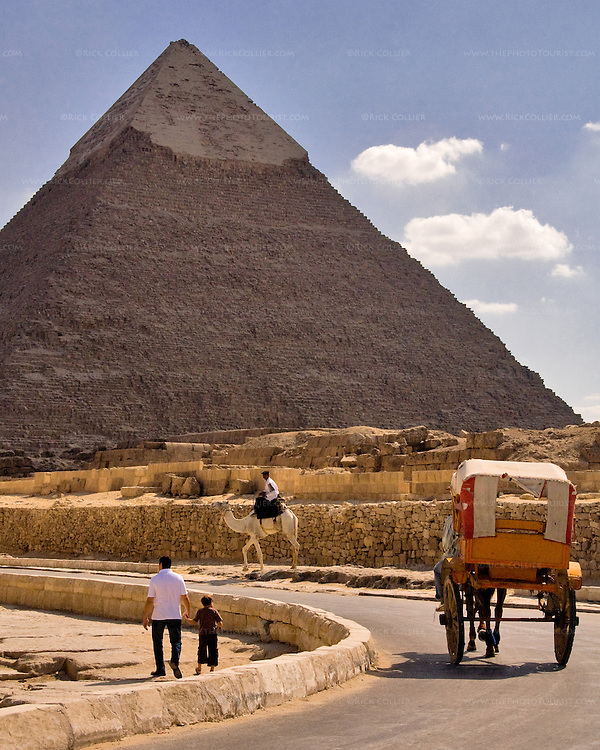 """Giza, Cairo, Egypt -- Tourists wander around the pyramids under the watchful eye of a Tourism and Antiquities policeman on camel.  (The """"second"""" pyramid of Khafre [Kephren] is in the background). © Rick Collier / RickCollier.com."""