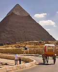 "Giza, Cairo, Egypt -- Tourists wander around the pyramids under the watchful eye of a Tourism and Antiquities policeman on camel.  (The ""second"" pyramid of Khafre [Kephren] is in the background). © Rick Collier / RickCollier.com."
