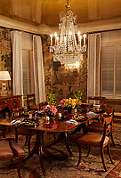 In a grand dining room, a table for six is laid for a Japanese dinner. An opulent crystal chandelier hangs above the table and the walls are covered in wallpaper with a Chinese scene motif.