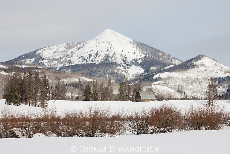 A secluded barn on Steamboat Lake is backdropped by Hahns Peak on a clear winter morning in Northwest Colorado.
