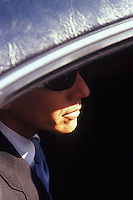 Man in suit in back seat of limousine<br />