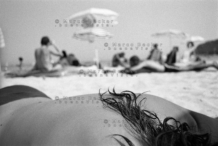 Capo Carbonara, Villasimius (Cagliari), bagnanti. La schiena di una ragazza in topless che prende il sole sdraiata sulla spiaggia di Porto Giunco --- Cape Carbonara, Villasimius (Cagliari), bathers. The back of a girl lying topless sun bathing on the beach at Porto Giunco