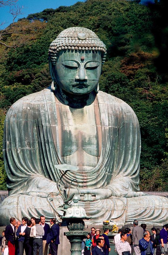 Japanese crowds gather under the Daibutsu; the famous statue of the Great Buddha. Kamakura, Kanagawa prefecture, Japan.