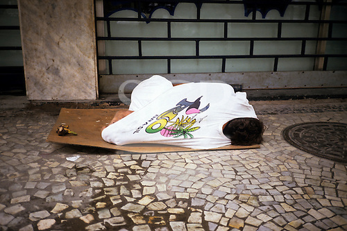 Rio de Janeiro, Brazil; child wearing a 'Rio Brazil' t-shirt sleeping on a piece of cardboard outside a barred building.