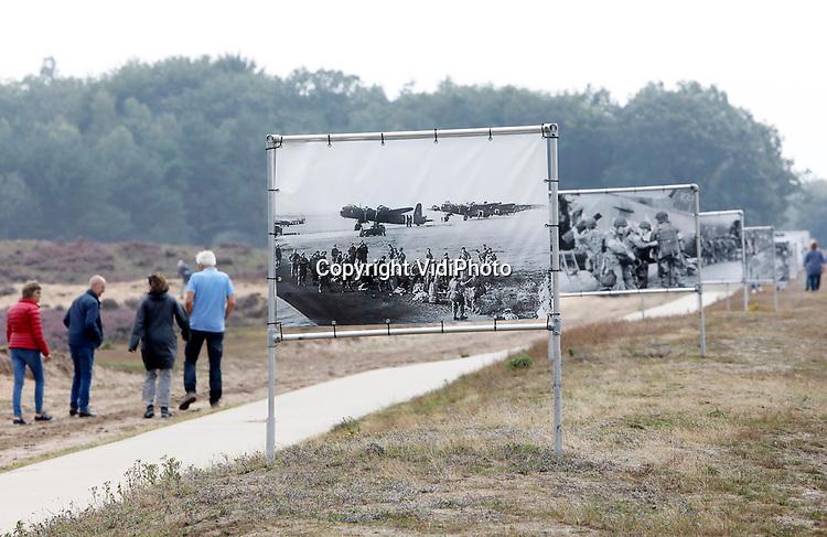 """Foto: VidiPhoto<br /> <br /> EDE – Topdrukte op de Ginkelse heide donderdag. Op de bijna laatste dat van de vakantie worden het vorig jaar onthulde herinneringsmonument  """"Vensters op het verleden"""" en de pasgeplaatste foto-expositie over operatie Market Garden en Nederlandse militaire missies massaal bezocht. Omdat de jaarlijkse luchtlandingen en Airborneherdenkingen op de heide bij Ede volgende maand vanwege Covid-19 niet doorgaan, nemen bezoekers nu de gelegenheid te baat om monument en tijdelijke expositie te bezoeken."""