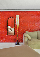 A modern bedroom with vibrant red painted brick walls. A contemporary floor lamp stands next to a sofa upholstered in a neutral fabric.