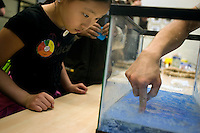 """Julie Park, 9, of Natick, Massachusetts, watches a demonstration of """"magic sand,"""" a hydrophobic substance, demonstrated by Satoru Emori, 3rd year grad student in Materials Science and Engineering, at MIT's Under the Dome open house in Cambridge, Massachusetts, USA?."""