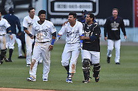 Asheville Tourists designated hitter Jonathan Piron (9) right fielder Jonathan Piron (2) and catcher Hamlet Marte (14) celebrate Daza's  walk off single after game one of a double header against the Kannapolis Intimidators at McCormick Field on May 21, 2016 in Asheville, North Carolina. The Tourists defeated the Intimidators in game one 3-2. (Tony Farlow/Four Seam Images)