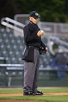 Home plate umpire Matt Carlyon checks a baseball between innings of the South Atlantic League game between the Hickory Crawdads and the Kannapolis Intimidators at Kannapolis Intimidators Stadium on April 8, 2016 in Kannapolis, North Carolina.  The Crawdads defeated the Intimidators 8-2.  (Brian Westerholt/Four Seam Images)