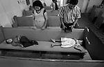 Octavio Cruz and his wife Isabel Cruz pray while their children Octavio, 5, and Karina, 2, nap during a church service in Warsaw, NC.