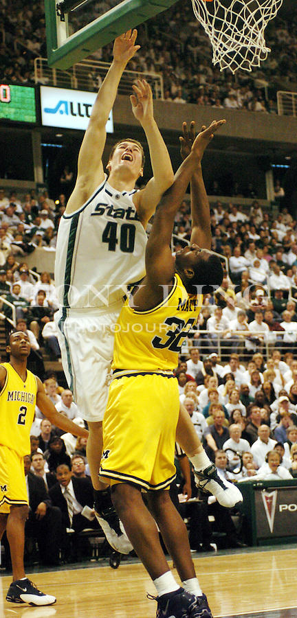 Spartan Paul Davis (40) overpowers Michigan junior J.C. Mathis (32) in a shot at basket during the Wolverines' 54-71 loss to Michigan State on Saturday, January 17, 2004 at the Breslin Center in East Lansing. Davis was the Spartan's lead scorer in the game, combining for 22 points. (TONY DING / The Michigan Daily)