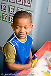 Education Preschool 4-5 year olds smiling boy at water table looking to side vertical