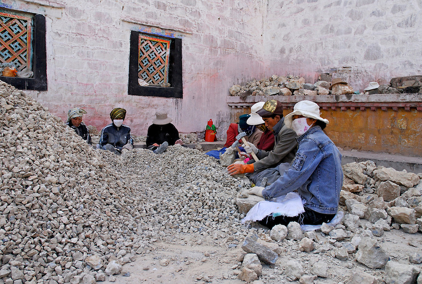 Tibetan workers, behind the Jokhang Temple, breaking stone for nearby construction, Lhasa, Tibet.