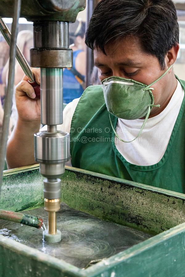 Antigua, Guatemala.  Jade Worker Polishing Jade.