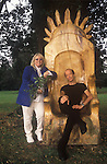 Dwina Gibb and Robin Gibb of the pop group Bee Gees 2000s at their home in the Home Counties UK. Dwina is a Druid and she is seen here in their garden , Robin sitting in an oak throne, with rising sun symbol. Dwina is holding a sprig of oak leaves.