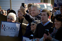 """Romney supporters gather to listen to Republican presidential candidate Mitt Romney, former governor of Massachusetts, as he speaks during a rally in Manchester, New Hampshire, on Sat. Dec. 3, 2011. The rally was called, """"Earn It with Mitt,"""" and was designed to bolster local efforts to help Romney """"earn"""" voters' support for the upcoming Republican primary."""