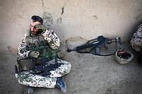 Afghanistan, 25.10.2011, Nawabad. Ein Soldat wischt sich in einer Marschpause die Stirn ab. Die in Kundus stationierte 3. Task Force (ISAF) der Bundeswehr beginnt im Oktober 2011 die mehrtaegige Operation Orpheus. Durch Patrouillen in und um die Kleinstadt Nawabad (Dirstrikt Chahar Dareh) westlich von Kundus, Nordafghanistan, versuchen die rund 100 Infanteristen Rueckzugsorte Aufstaendischer unmoeglich zu machen. Unterstuetzt werden sie dabei durch einen Zug afghanischer Soldaten. A private wipes his forehead during a break at the roadside. In October 2011 Kunduz based 3.Task Force started a several days operation in and around Nawabad (District Chahar Dareh), west of Kunduz, northern Afghanistan. During the Operation Orpheus about 100 german infantry soldiers went out for patrols through the town and surrounding areas, which were expected as a retreat zone of insurgents. A platoon of afghan soldiers supports the german forces. © Timo Vogt/Est&Ost, NO MODEL RELEASE !!