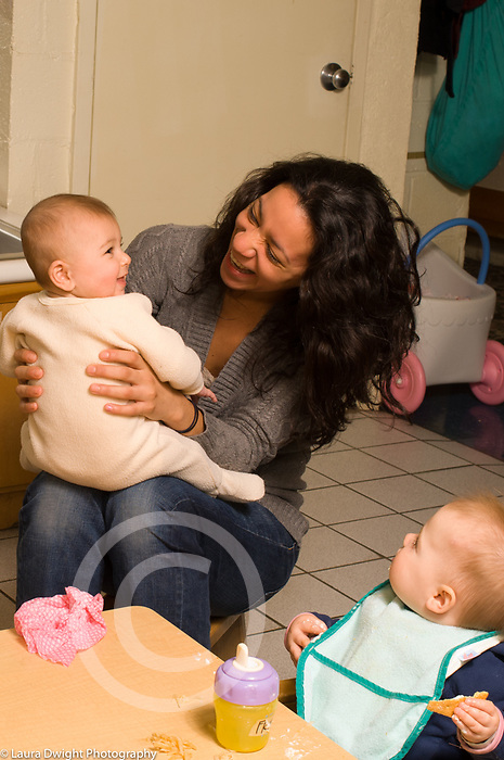 Day Care Center caregiver laughing with baby as another baby looks on