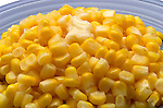 close up of side dish with cut corn with pat of butter on top