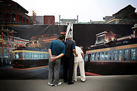 """CHINA. Beijing. People peer through a fence, trying to catch a glimpse of the new Qianmen shopping district. In recent years construction has boomed in Beijing as a result of the country's widespread economic growth and the awarding of the 2008 Summer Olympics to the city. For Beijing's residents however, it seems as their city is continually under construction with old neighborhoods regularly being razed and new apartments, office blocks and sports venues appearing in their place. A new Beijing has been promised to the people to act as a showcase to the world for the 'new' China. Beijing's residents have been waiting for this promised change for years and are still waiting, asking the question """"Where's the new Beijing?!"""". 2008"""