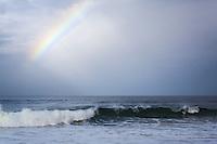 A slice of rainbow glows above a gentle wave along California's coast.