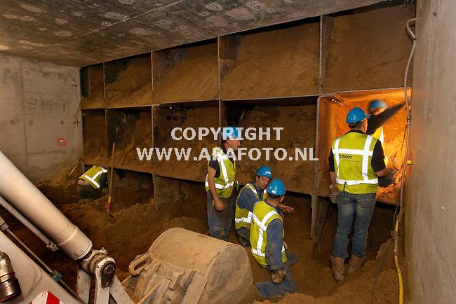 Arnhem 250910 Fietstunnel onder spoordijk blijft steken.<br />  Deskundigen van aannemer en Prorail inspecteren de verbogen messen aan de voorzijde van de fietstunnel.<br /> <br /> Foto Frans Ypma APA-foto
