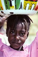 Near Niamey, Niger.  Fulani Girl Carrying Bucket of Water on Head.