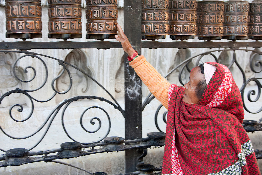 Kathgmandu, Nepal. Woman Spinning Prayer Wheels at Swayambhunath Temple.