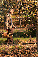 Hugues Martin, the owner of the truffles farm with a wicker basket to collect the truffles, showing how you use a twig to find truffles, when you see truffle flies fly flying when you stir the leaves on the ground you know that there is a truffle in the ground Truffiere de la Bergerie (Truffière) truffles farm Ste Foy de Longas Dordogne France