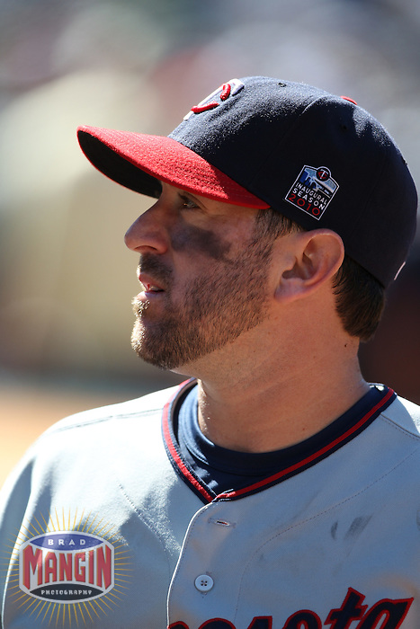 OAKLAND, CA - JUNE 6:  Nick Punto #8 of the Minnesota Twins stands in the dugout after the game against the Oakland Athletics at the Oakland-Alameda County Coliseum on June 6, 2010 in Oakland, California. Photo by Brad Mangin