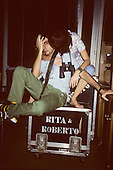 "Brazil. Rita Lee & Roberto Carvalho on tour sitting on a flight case marked ""Rita & Roberto"" with guitar strap and binoculars."