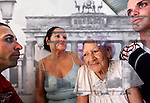This is the Cuban family (sister, nephews and 93-year-old mother) of a man who fled from Cuba to Florida during the Mariel Boatlift of 1980. The four have been separated from their uncle, son and brother for 35 years. It is blended with a faraway view of the Brandenburg Gate, as close as you could get from East Berlin before the fall of the Berlin Wall - photographed during one of few vacations my grandparents and father could take in the Communist years. International travel was limited to pre-approved countries within the Eastern Bloc (while Western nations were accessible with government approval only.) The merging of these images speaks of both the desire for and difficulty of emigration in repressed sociopolitical climates.  <br /> <br /> I've layered family photos taken in Bulgaria before the fall of the Berlin Wall with pictures I recently shot in Cuba, to reveal the visual and sociopolitical connections between the two. Both portions of this project - in Bulgaria and Cuba - were supported by The Pulitzer Center on Crisis Reporting.