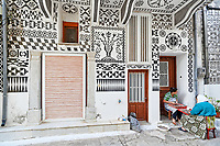 Local women work outside a traditional house decorated with the famous geometric scratch patterns in the medieval village of Pyrgi on the island of Chios, Greece