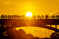 Bat watchers stand in silhouette agains a beautiful golden sunset on the Congress Avenue Bridge in downtown Austin, Texas.