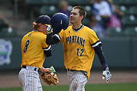 Ryne Simon (12) of the UNC Greensboro Spartans is congratulated after scoring a run in a game against the Furman Paladins in the title game of the Southern Conference Championship series on Sunday, May 28, 2017, at Fluor Field at the West End in Greenville, South Carolina. UNCG won, 13-1. (Tom Priddy/Four Seam Images)
