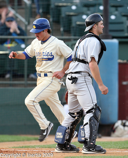 SIOUX FALLS, SD - MAY 14:  Joe Anthonsen of the Sioux Falls Canaries crosses home plate in the first inning past Jeff Desmidt catcher for St. Paul Saints Thursday night at the Sioux Falls Stadium. (Photo by Dave Eggen/Inertia)